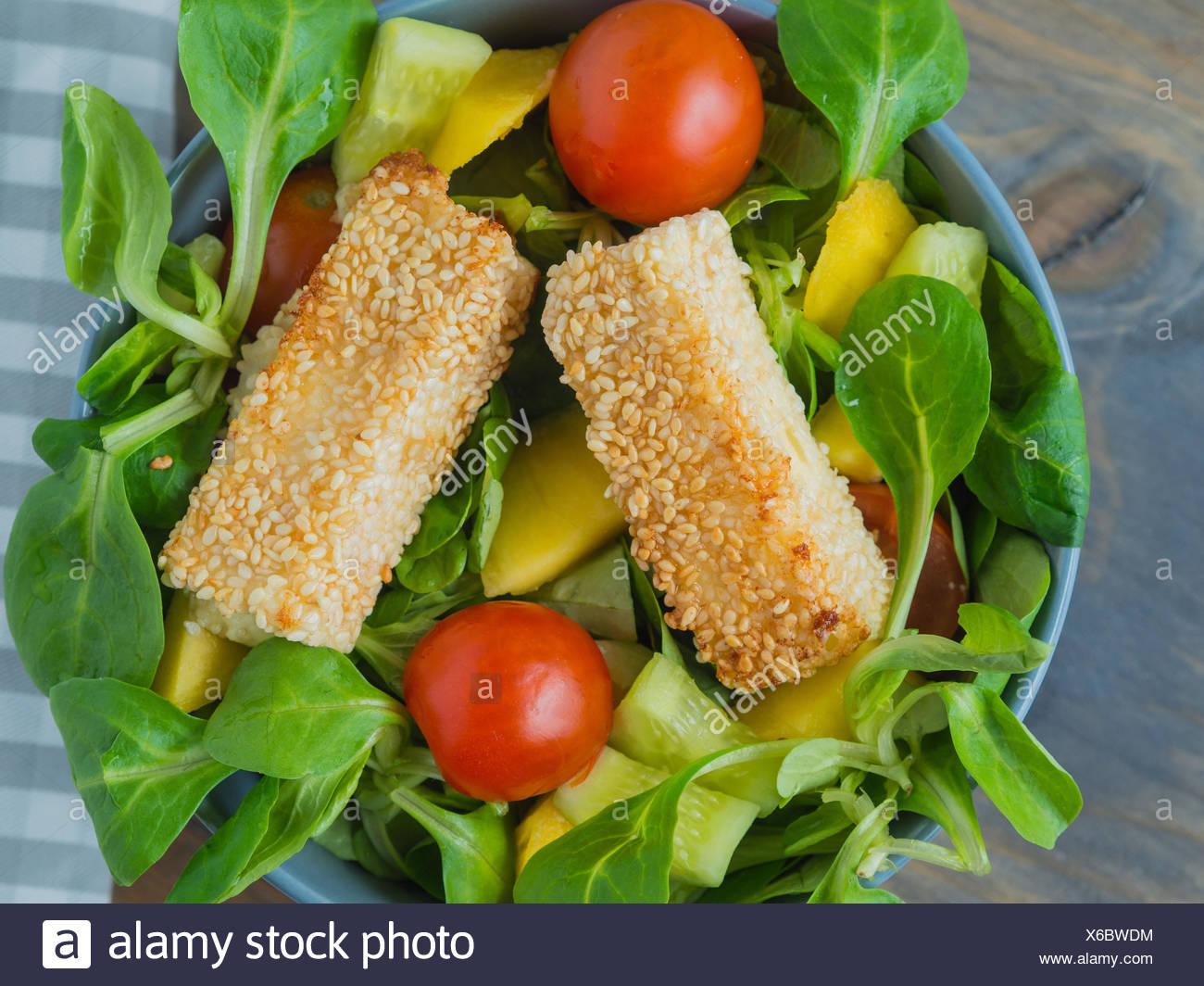 Cotto il formaggio feta in crosta di sesamo su Insalata mista con mango Immagini Stock