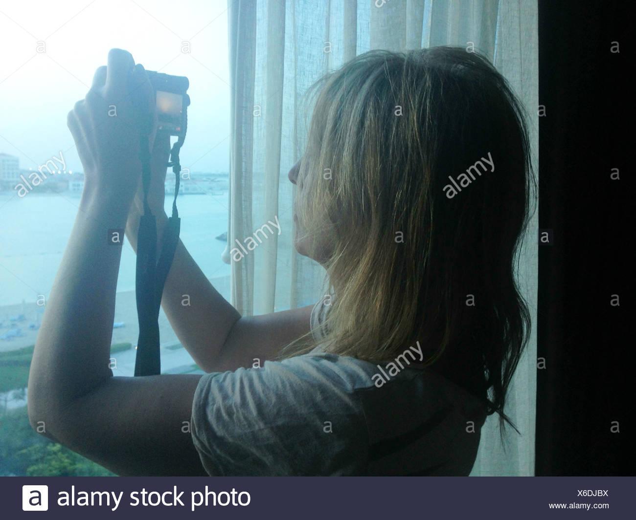Donna prendendo ancora fuori della finestra Immagini Stock