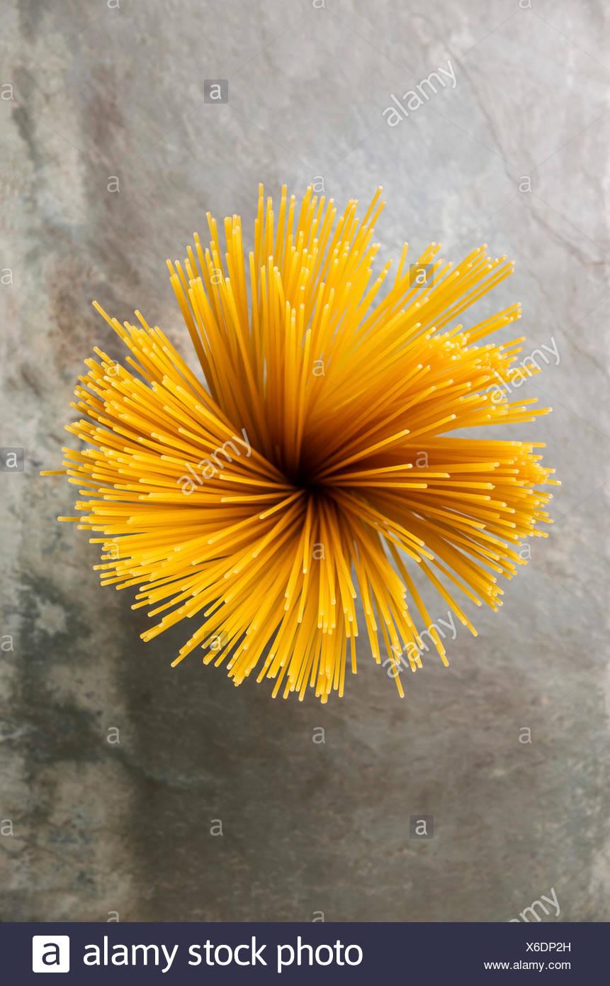 Vista superiore forma di fiore mazzo di spaghetti sulla pietra grigia sullo sfondo di ardesia Immagini Stock
