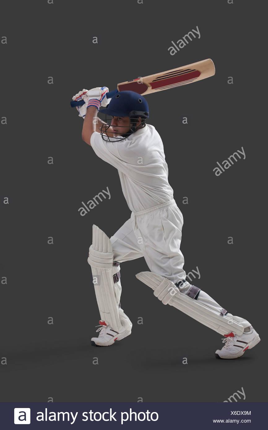 Giovane maschio giocatore giocare a cricket isolate su uno sfondo grigio Immagini Stock