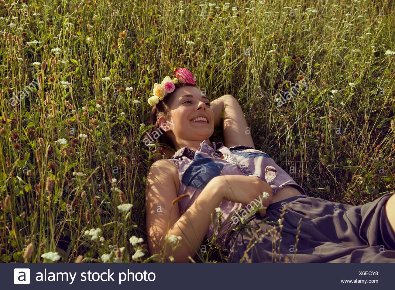 Giovane donna sdraiata nel prato con fiori nei capelli Foto Stock