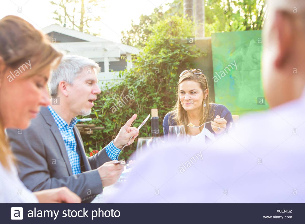 Adulti maturi di mangiare e parlare insieme al party in giardino tavolo Immagini Stock