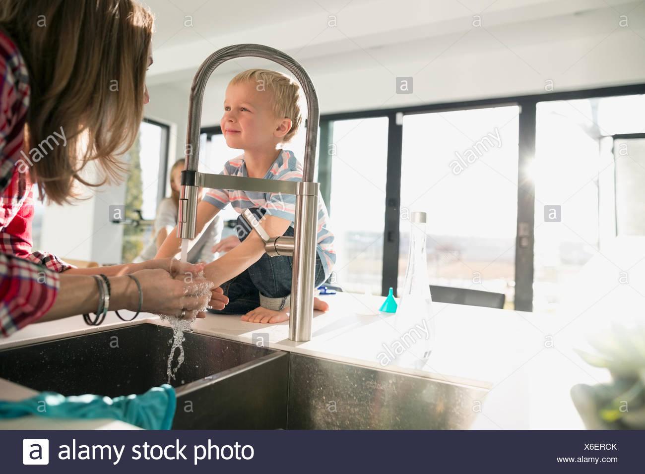 Madre lavando le mani nel lavello da cucina Immagini Stock
