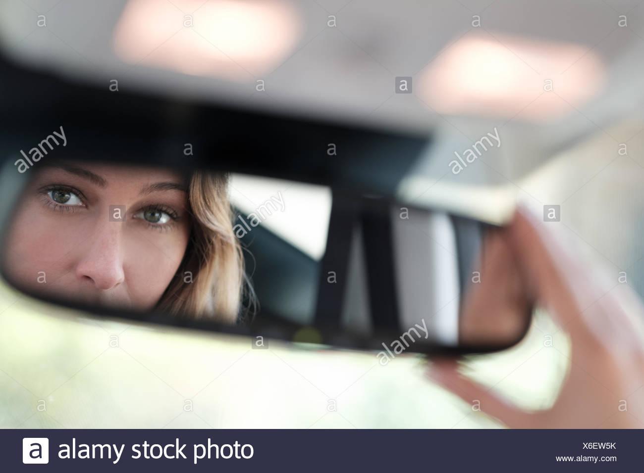 Donna volto riflesso in specchietto retrovisore Immagini Stock