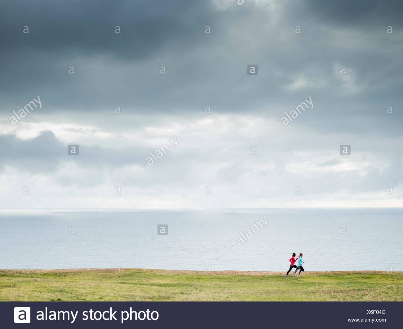Due donne a fare jogging lungo la costa in guide di scorrimento Immagini Stock