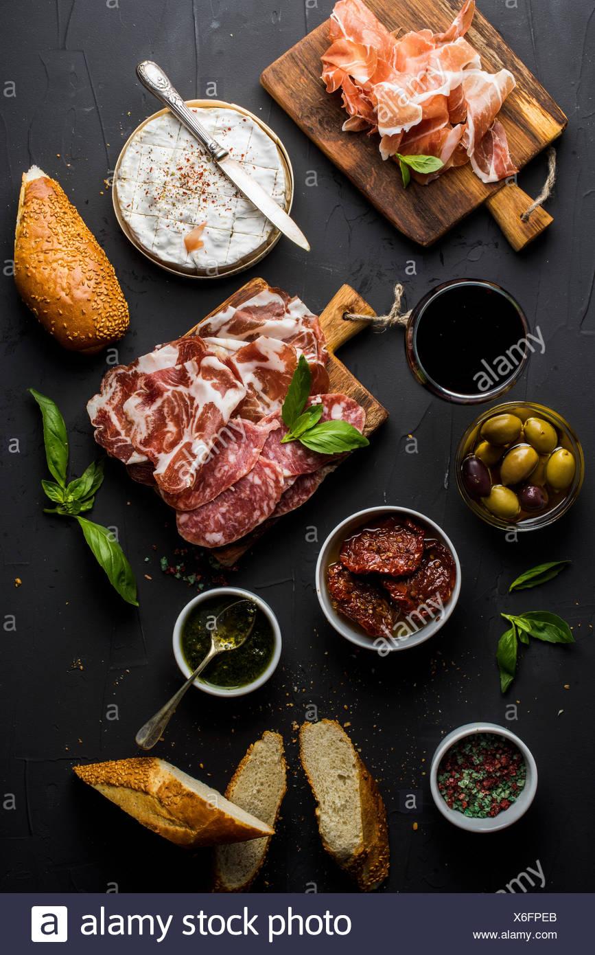 Vino snack set con vuoto tavola di legno in centro. Bicchiere di rosso, selezione di carne, mediterraneo olive, pomodori secchi, baguet Immagini Stock