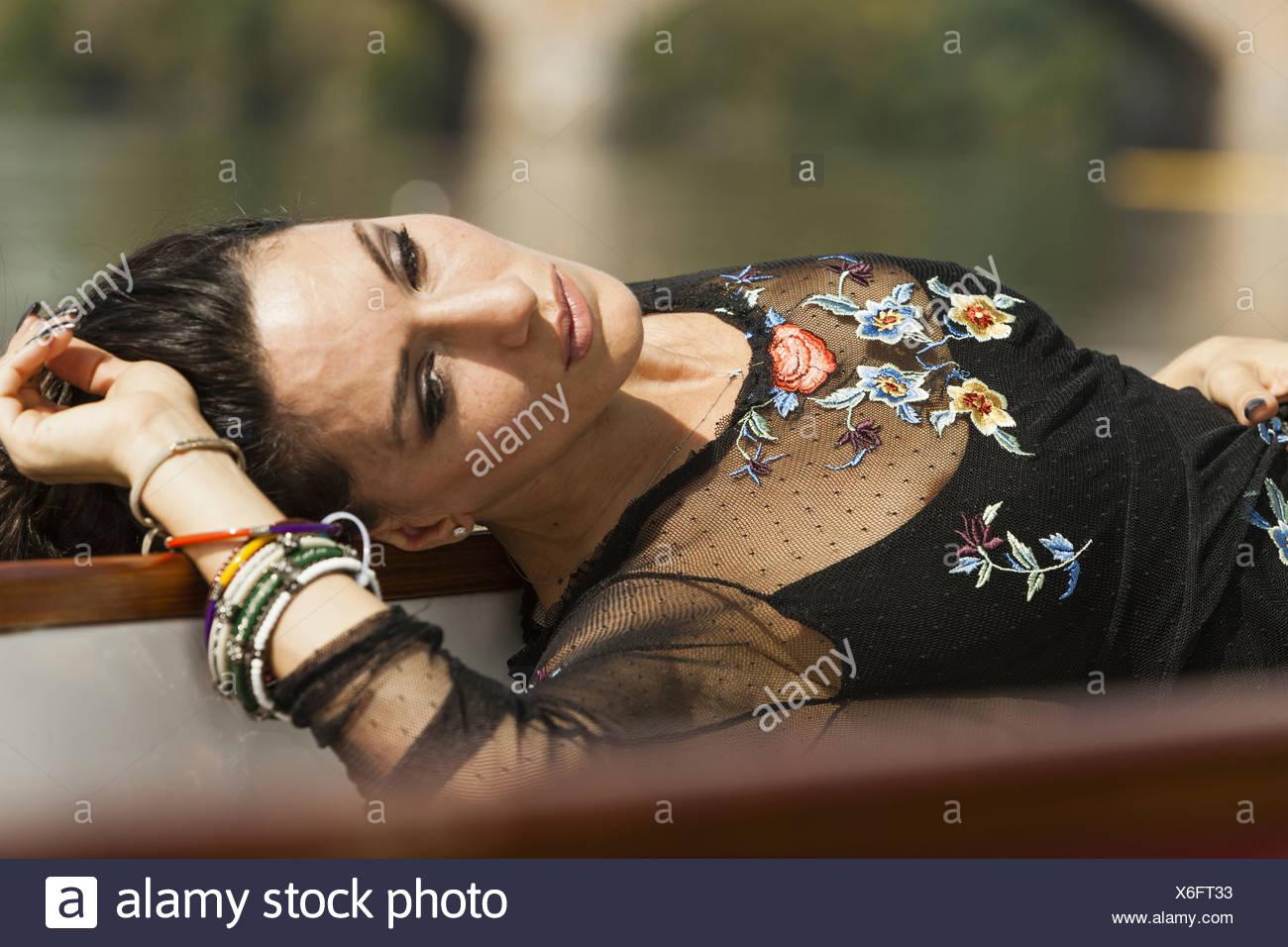 Una donna sdraiata sulla schiena, indossando un top nero con maniche a strapiombo e braccialetti di ricamo sul suo braccio Pennsylvania USA Foto Stock