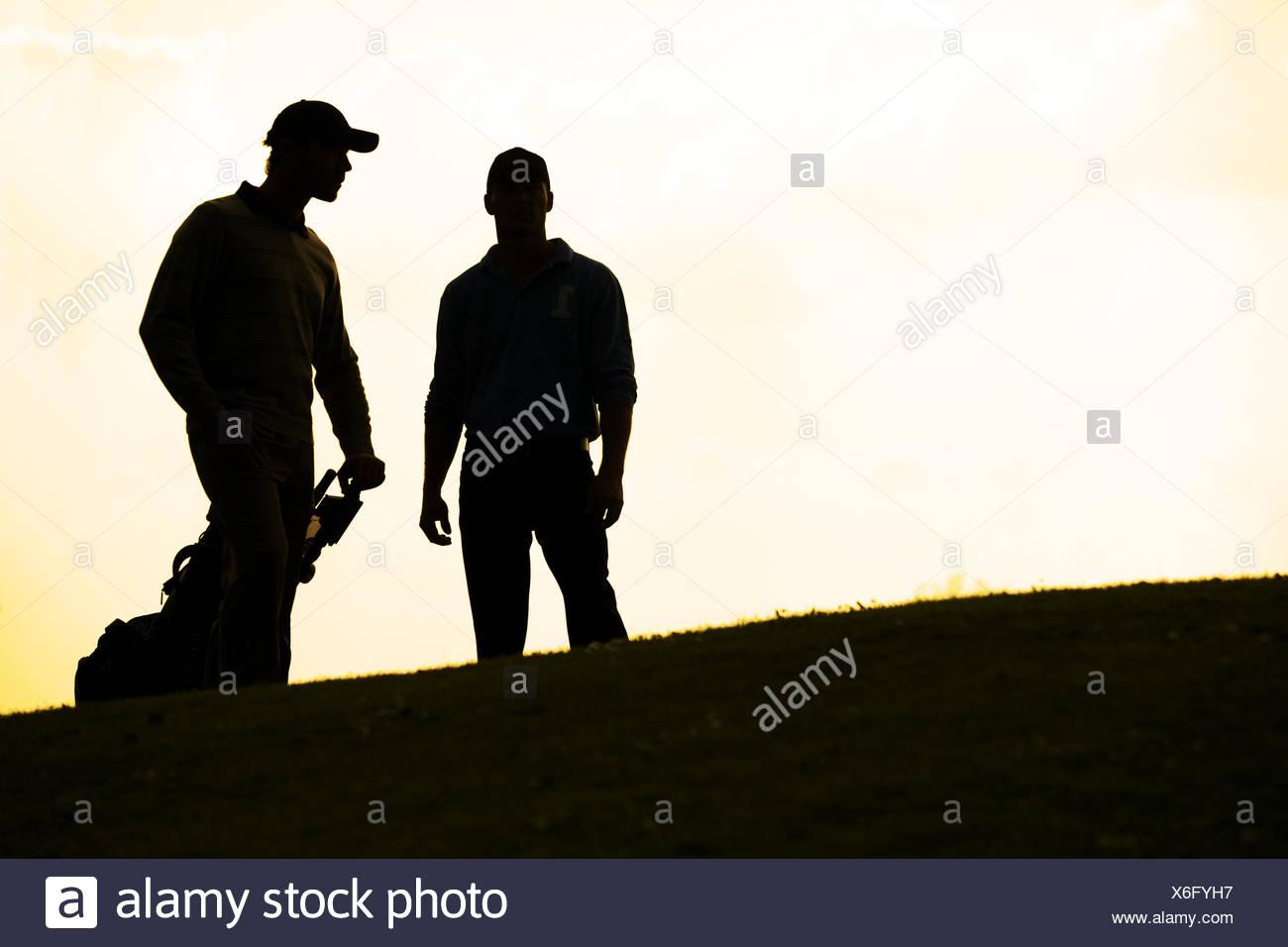 Silhouette di giovani uomini in piedi in campo da golf con trolley Immagini Stock