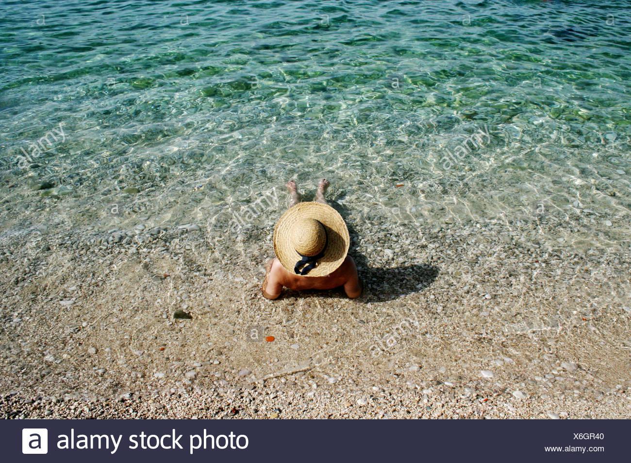 Croazia, donna con cappello di paglia per prendere il sole Immagini Stock