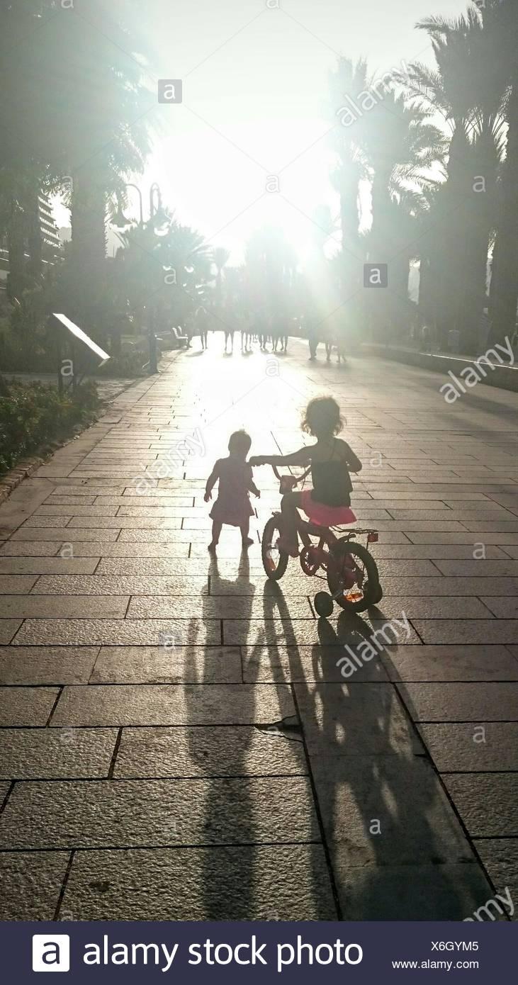 Vista posteriore di due bambini con bicicletta all'aperto Immagini Stock