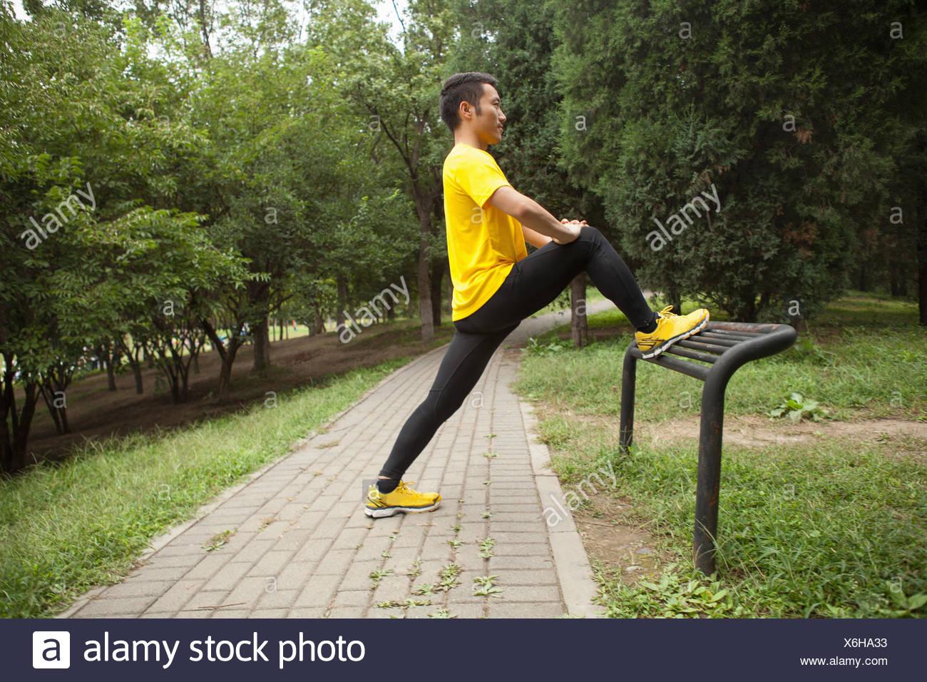 Giovane maschio runner il riscaldamento in posizione di parcheggio Immagini Stock