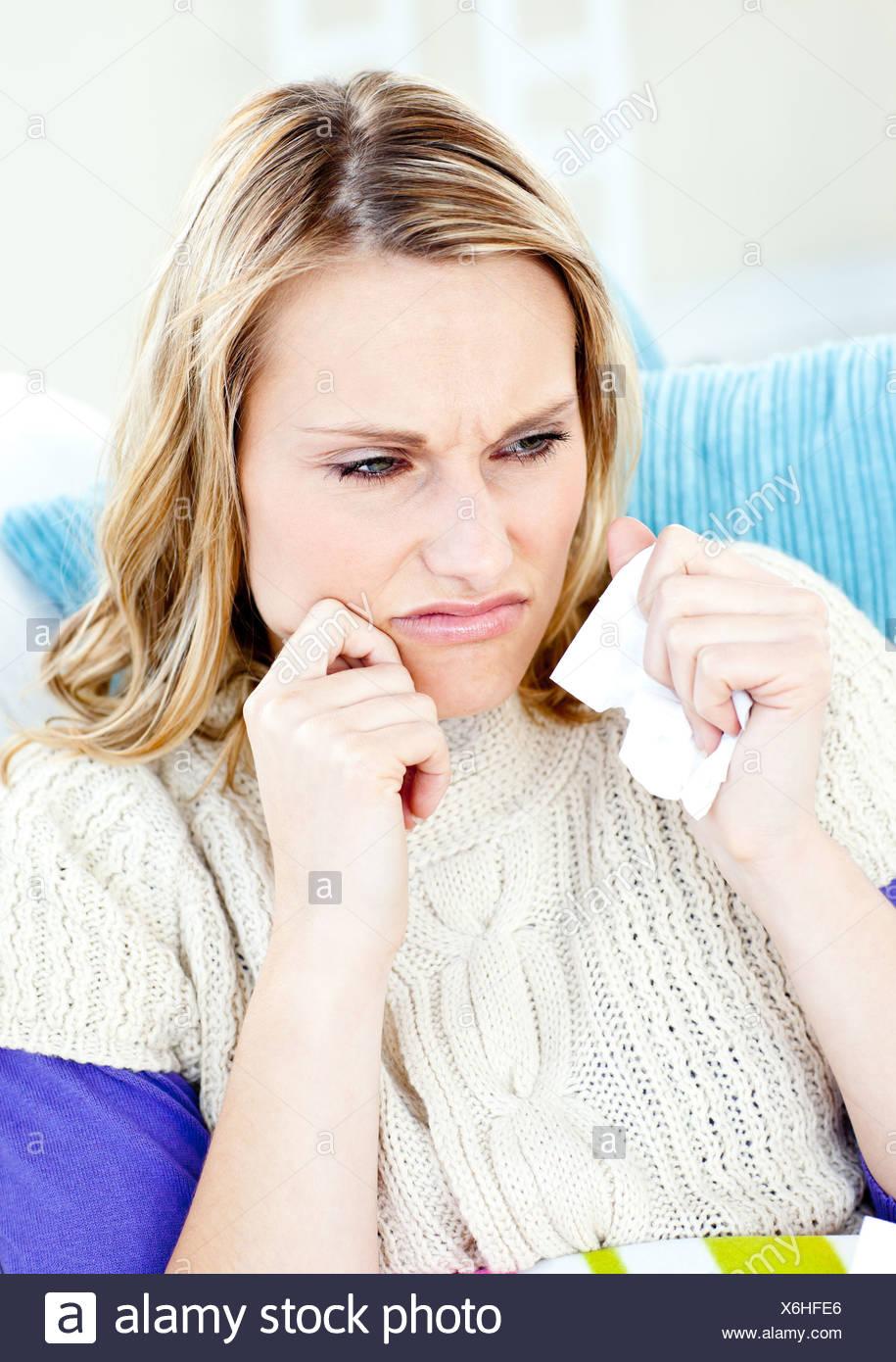 Abbattuto donna sdraiata su un divano con i tessuti Immagini Stock