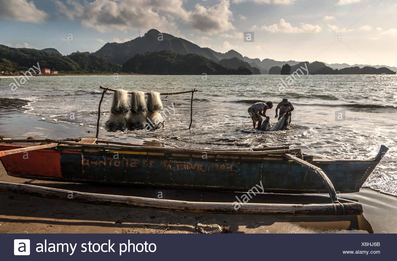 Gli uomini tendono reti da pesca Immagini Stock