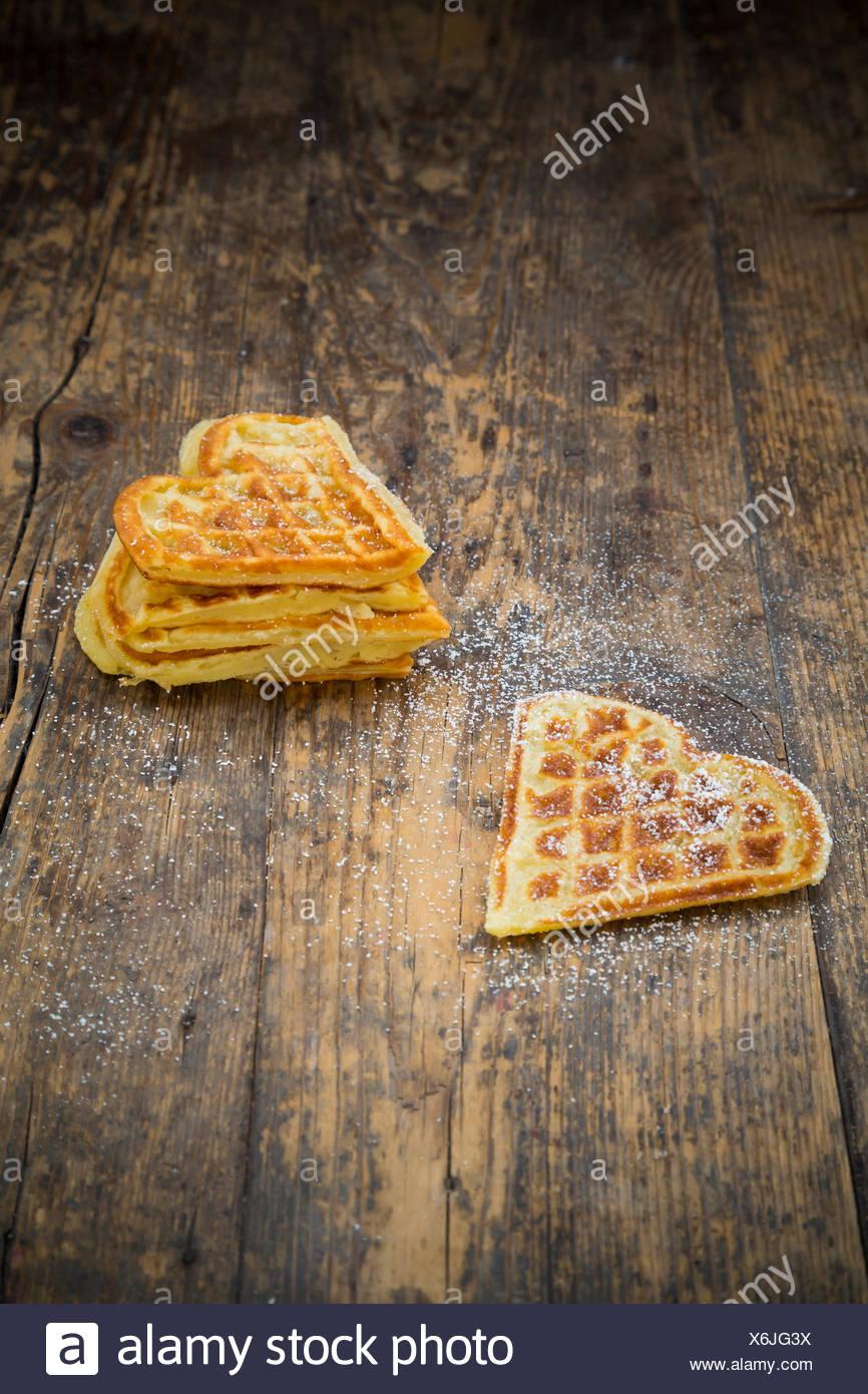 A forma di cuore ad cialde spolverati con zucchero a velo sul legno scuro Immagini Stock