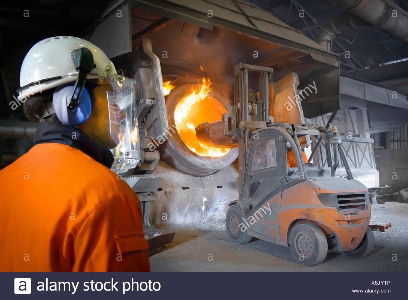 Lavoratore in abbigliamento protettivo guarda carrello a forno in fonderia alluminio immagine scaricata dal al 6:42 il 13/0 Immagini Stock