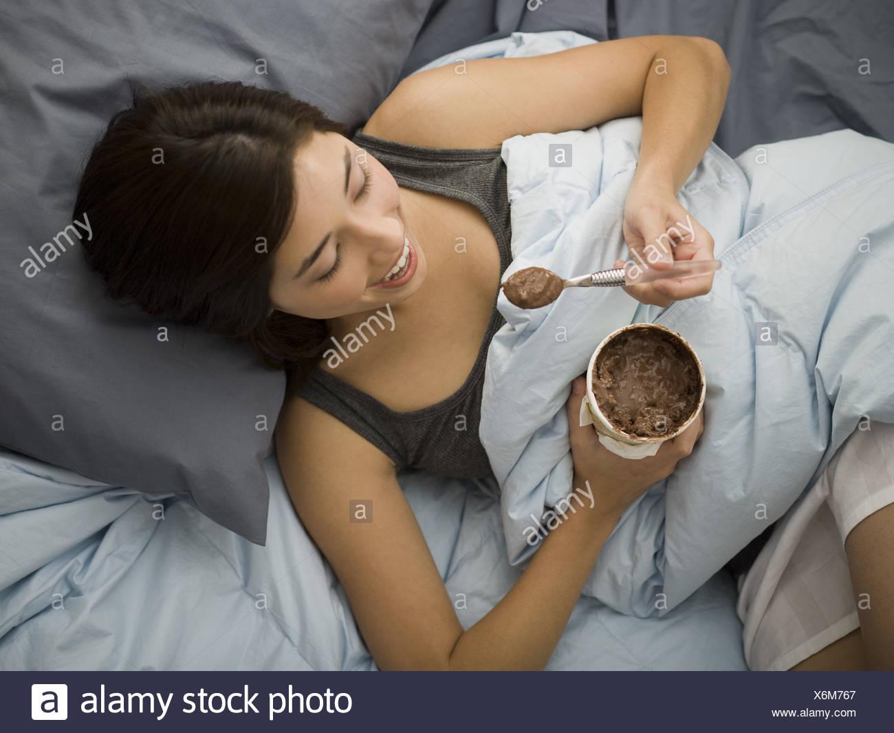 Donna sdraiata nel letto fuoriuscita di gelato al cioccolato sulla coperta Immagini Stock