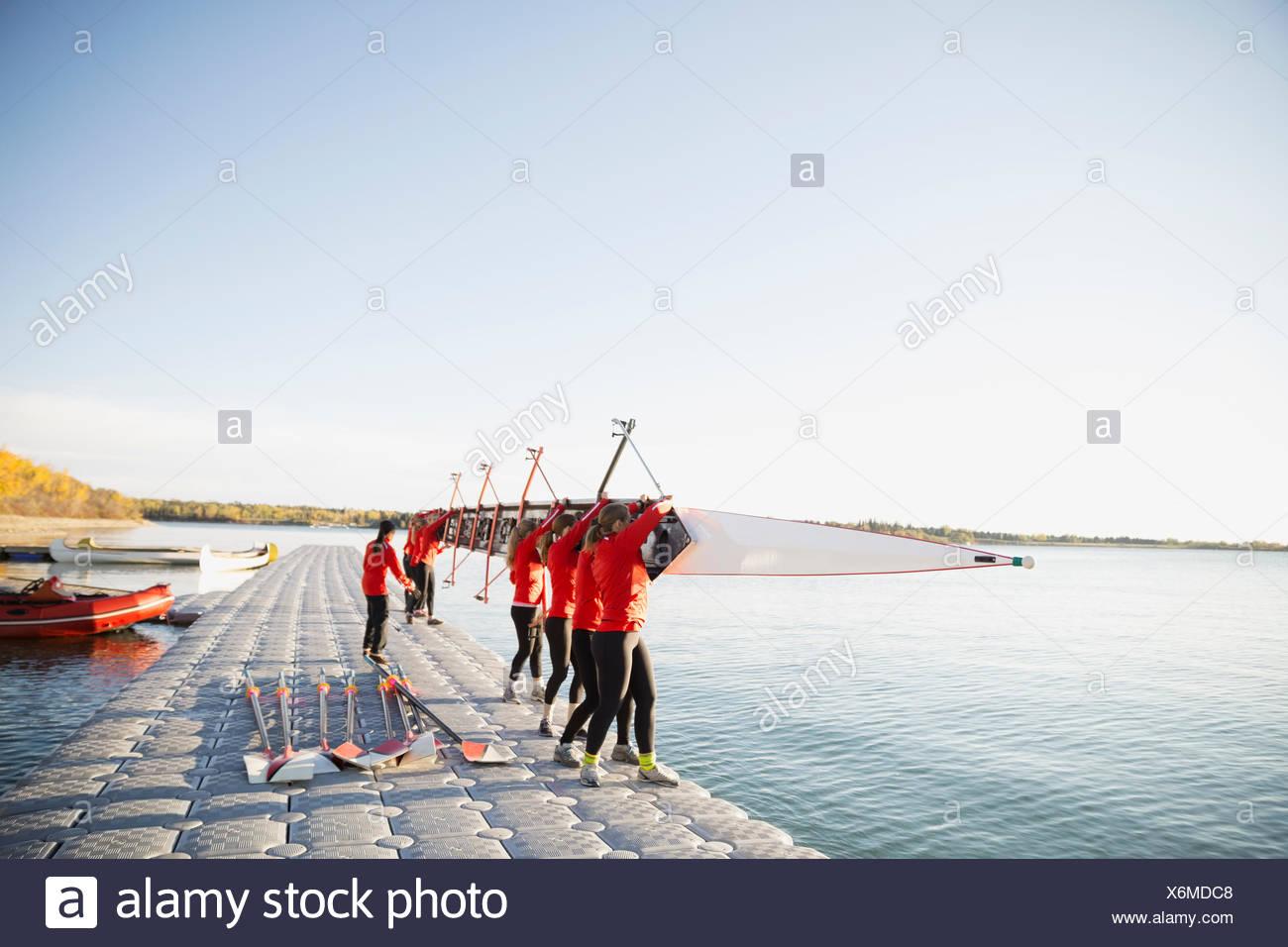 Il team di canottaggio holding scull a waterfront Immagini Stock
