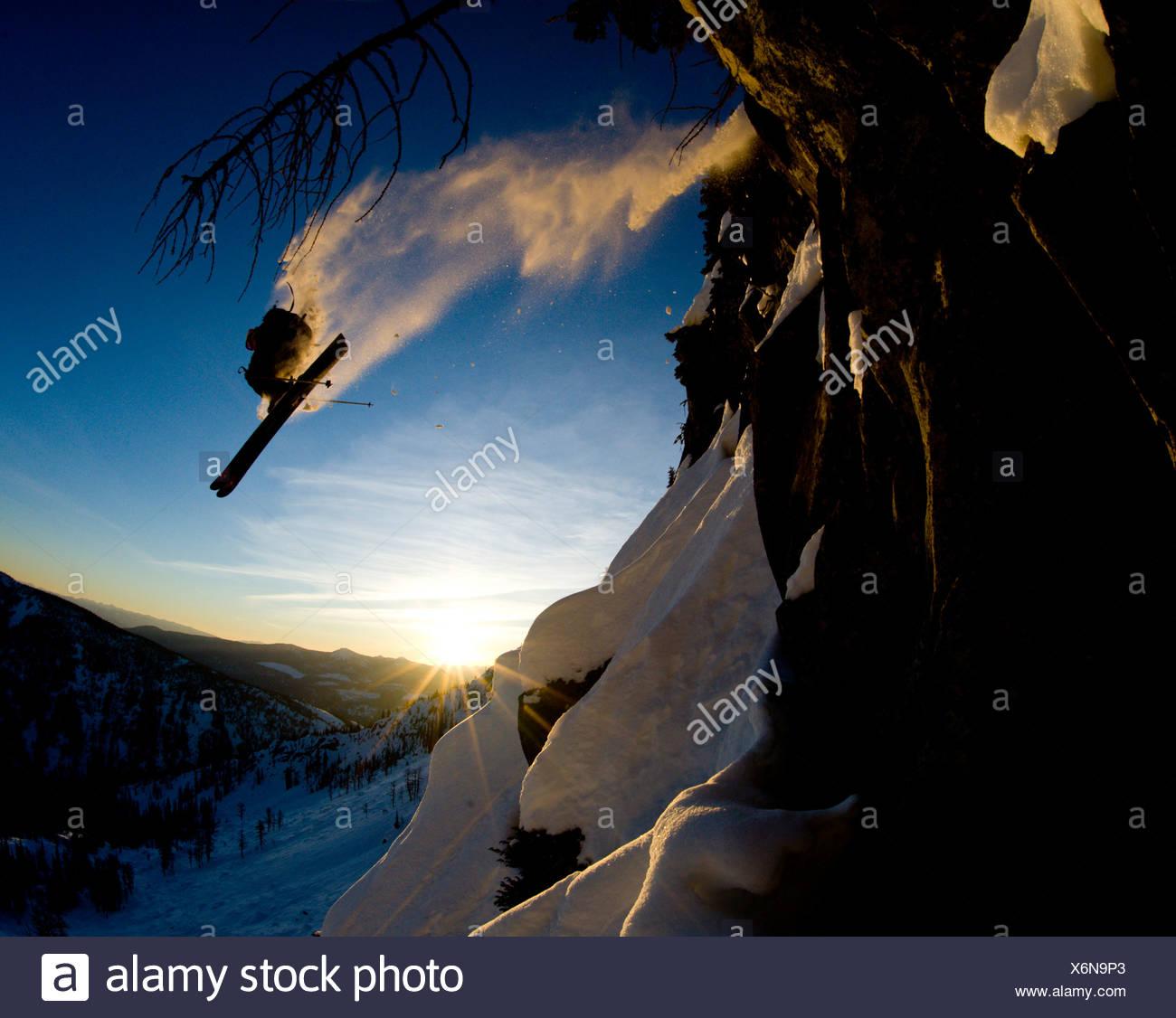 Un giovane maschio sciatore prende aria enorme da un dirupo nel backcountry vicino a Whitewater Resort invernale, British Columbia, Canada Immagini Stock