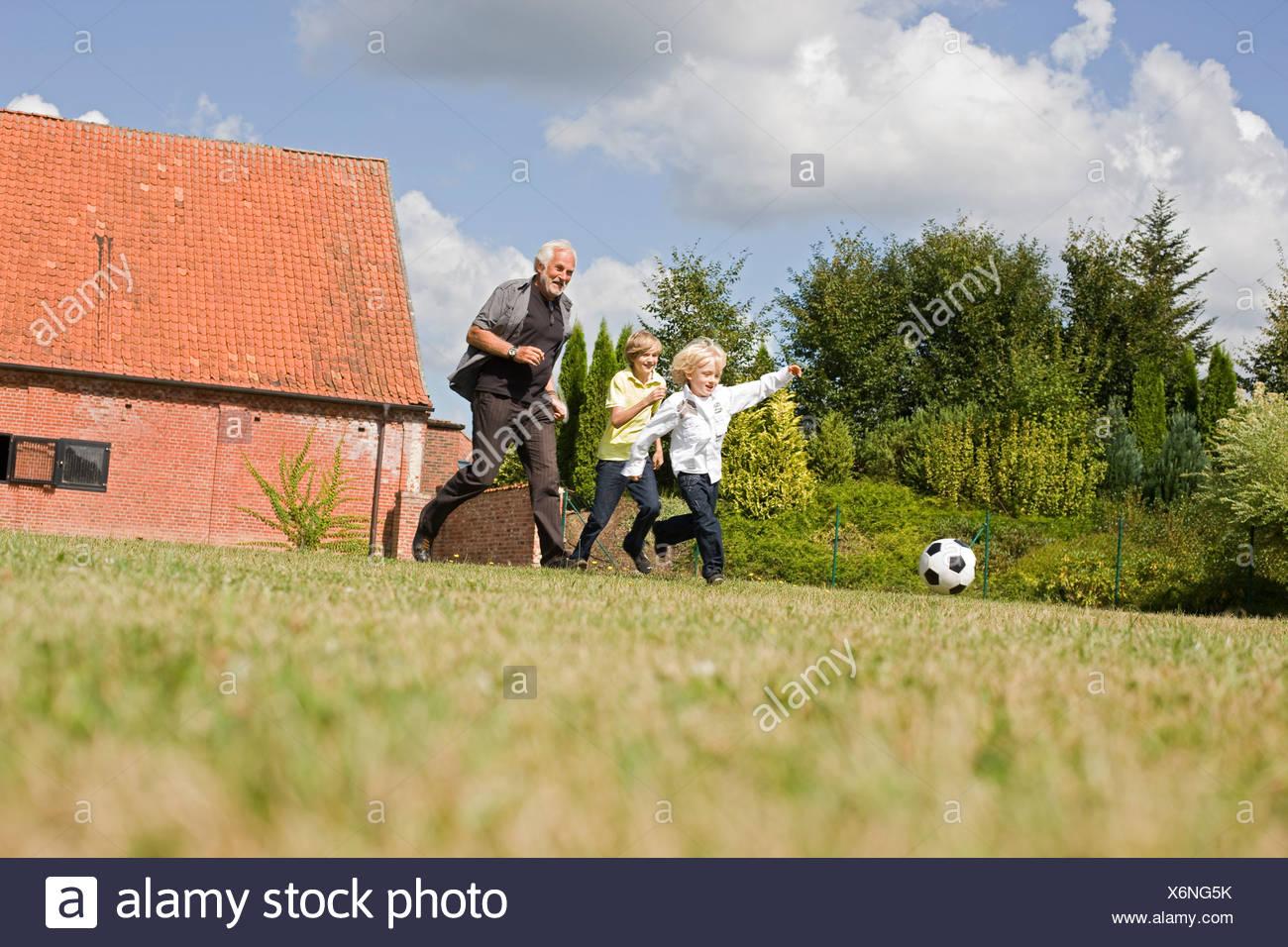 Nonno e i bambini a giocare a calcio Immagini Stock