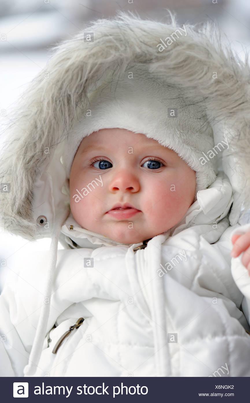 Baby, 6 mese, avvolto in molto caldo abbigliamento invernale Immagini Stock