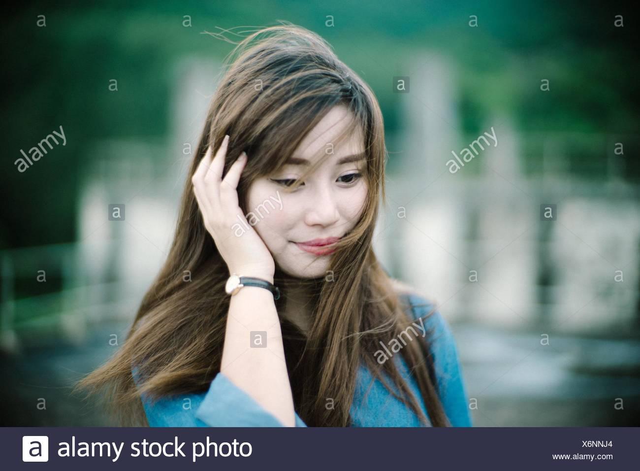 In primo piano della giovane donna sorridente mentre guardando verso il basso Immagini Stock