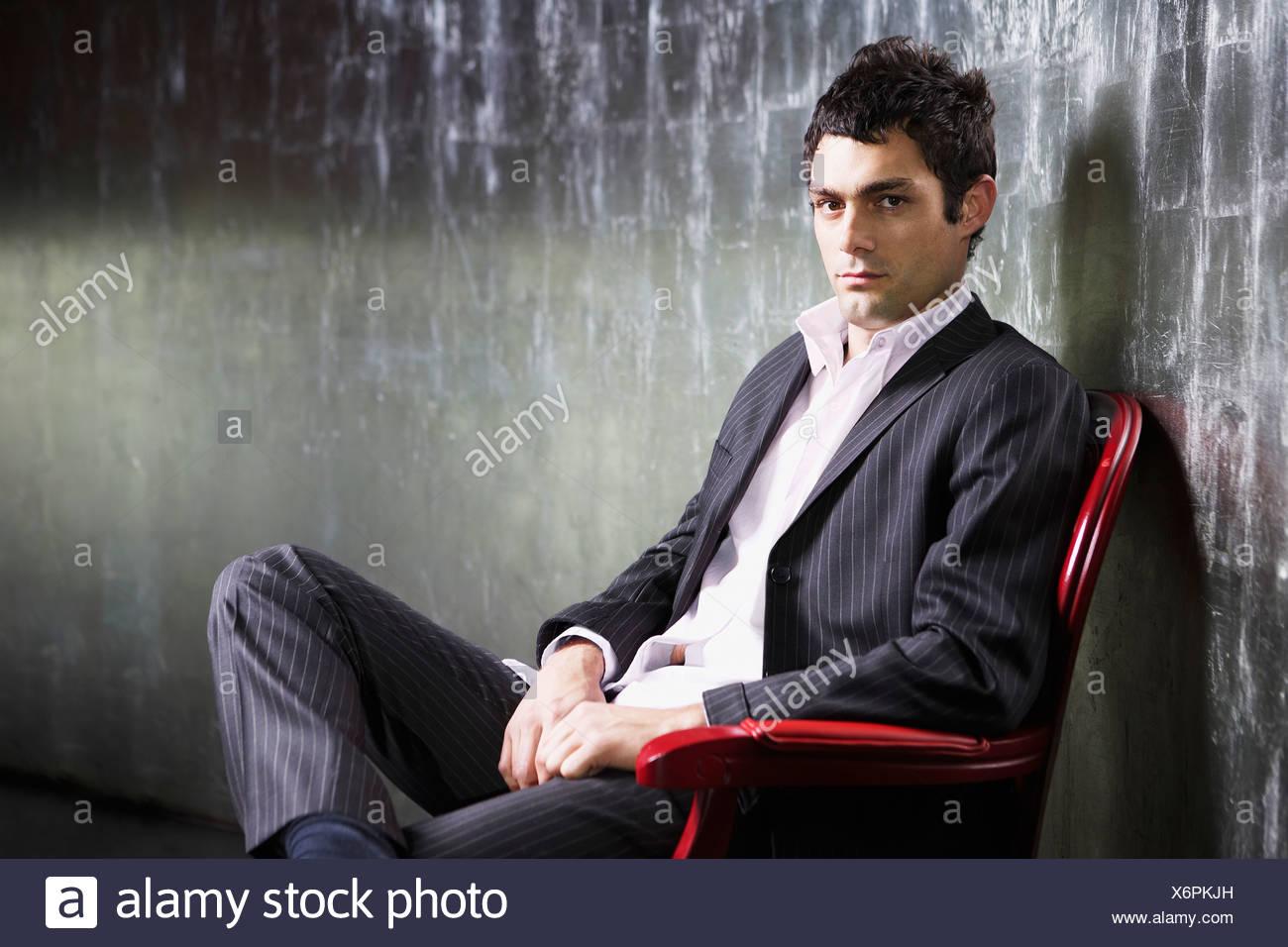 Elegante uomo seduto, gambe incrociate, in metallo camera, vista laterale Immagini Stock