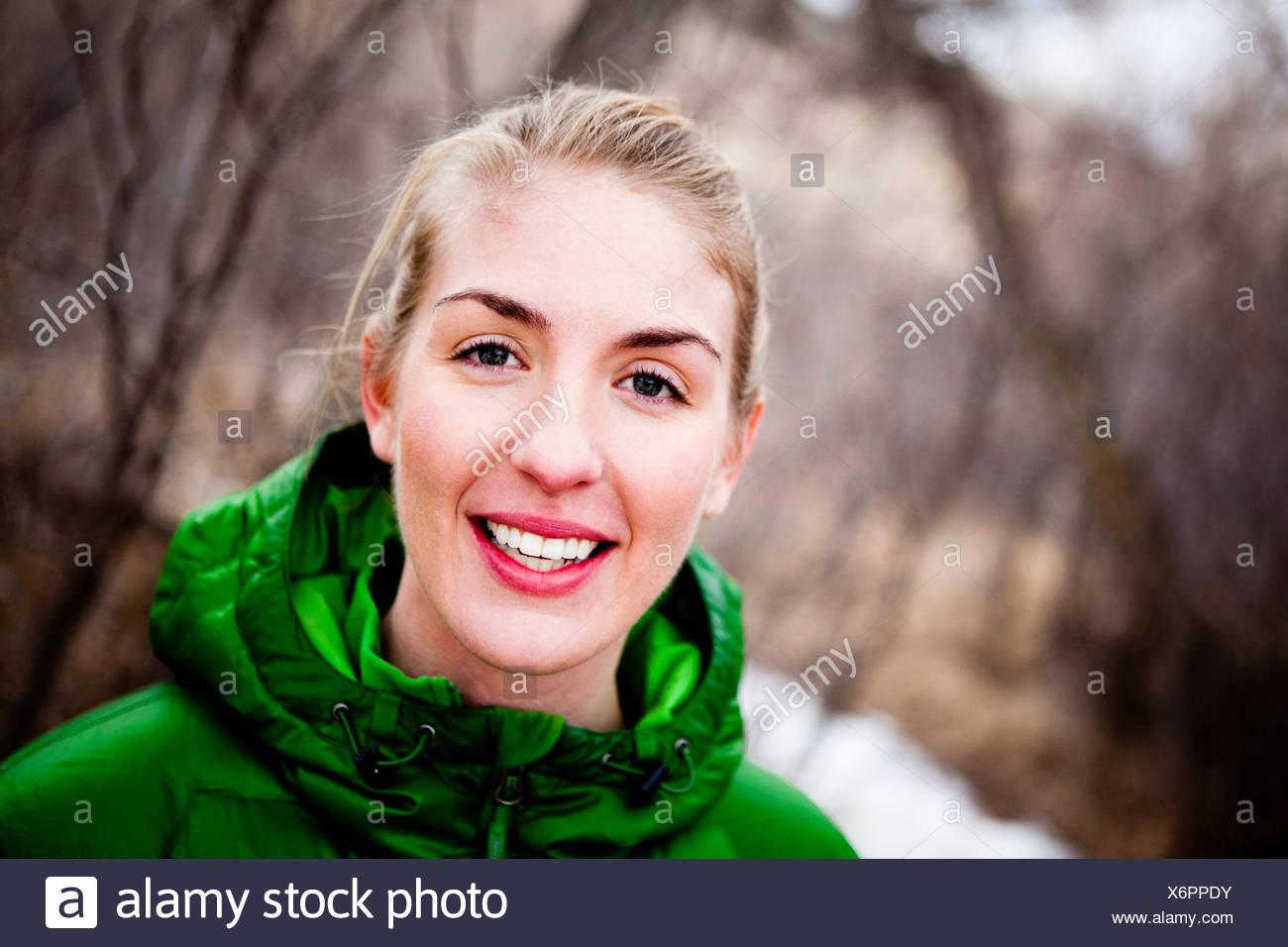 Una giovane donna corre un lungo coperto di neve sentiero sterrato attraverso sfrondato di alberi decidui appena a nord di Dixon serbatoio, in un freddo giorno Immagini Stock
