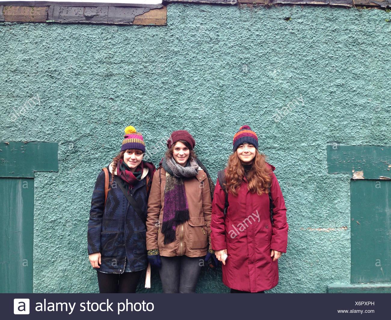 Tre donne in piedi contro un muro Immagini Stock
