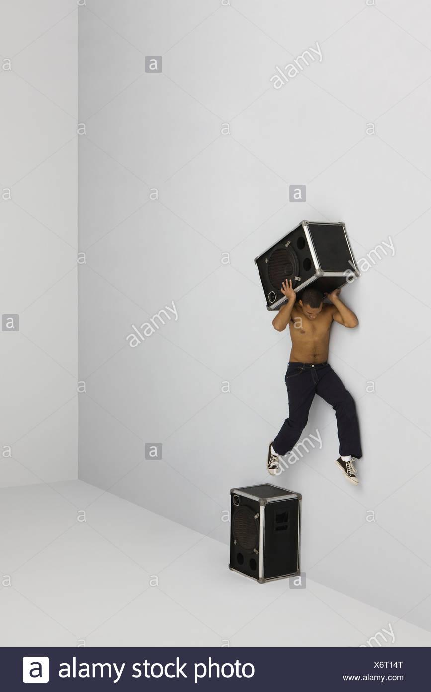 Uomo di saltare fuori di persico in cima porta altoparlante secondo altoparlante su spalle Immagini Stock