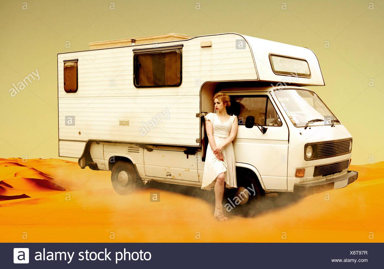 Germania, Berlino, giovane donna in piedi accanto al bus di campeggio nel deserto Foto Stock