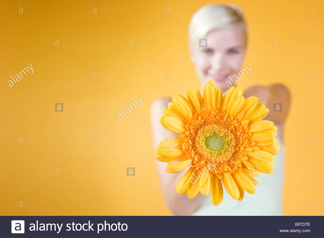 Una giovane donna tenendo un fiore di arancia Immagini Stock