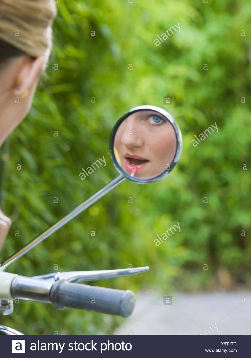 Donna che guarda la telecamera nel suo specchietto retrovisore Immagini Stock