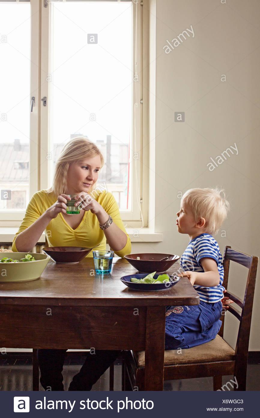 Finlandia, Helsinki, Kallio, madre e figlio al tavolo pranzo Immagini Stock
