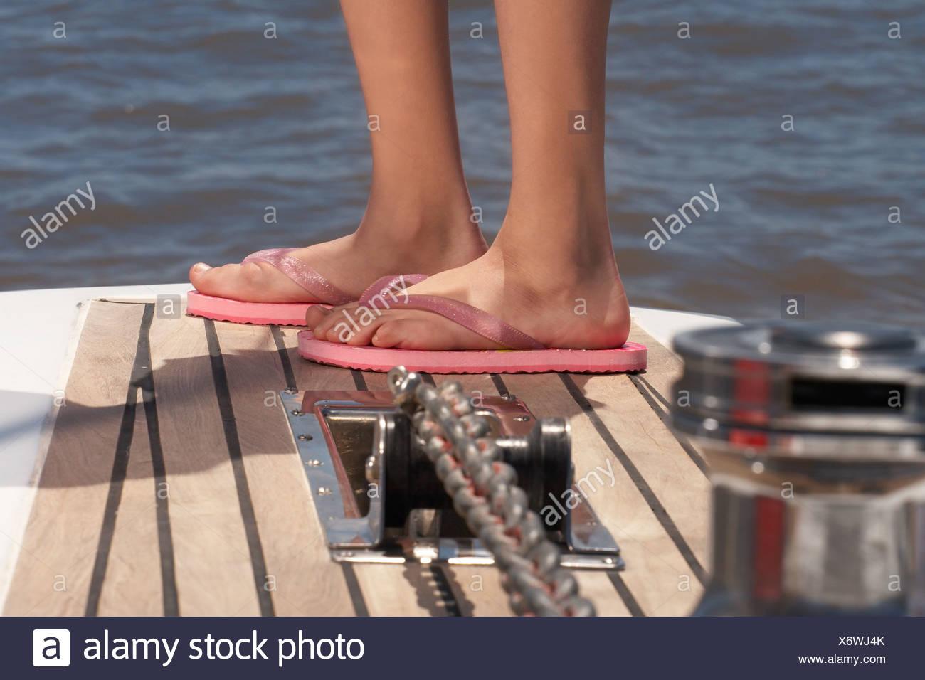 Dettaglio della ragazza in piedi indossando le infradito Immagini Stock
