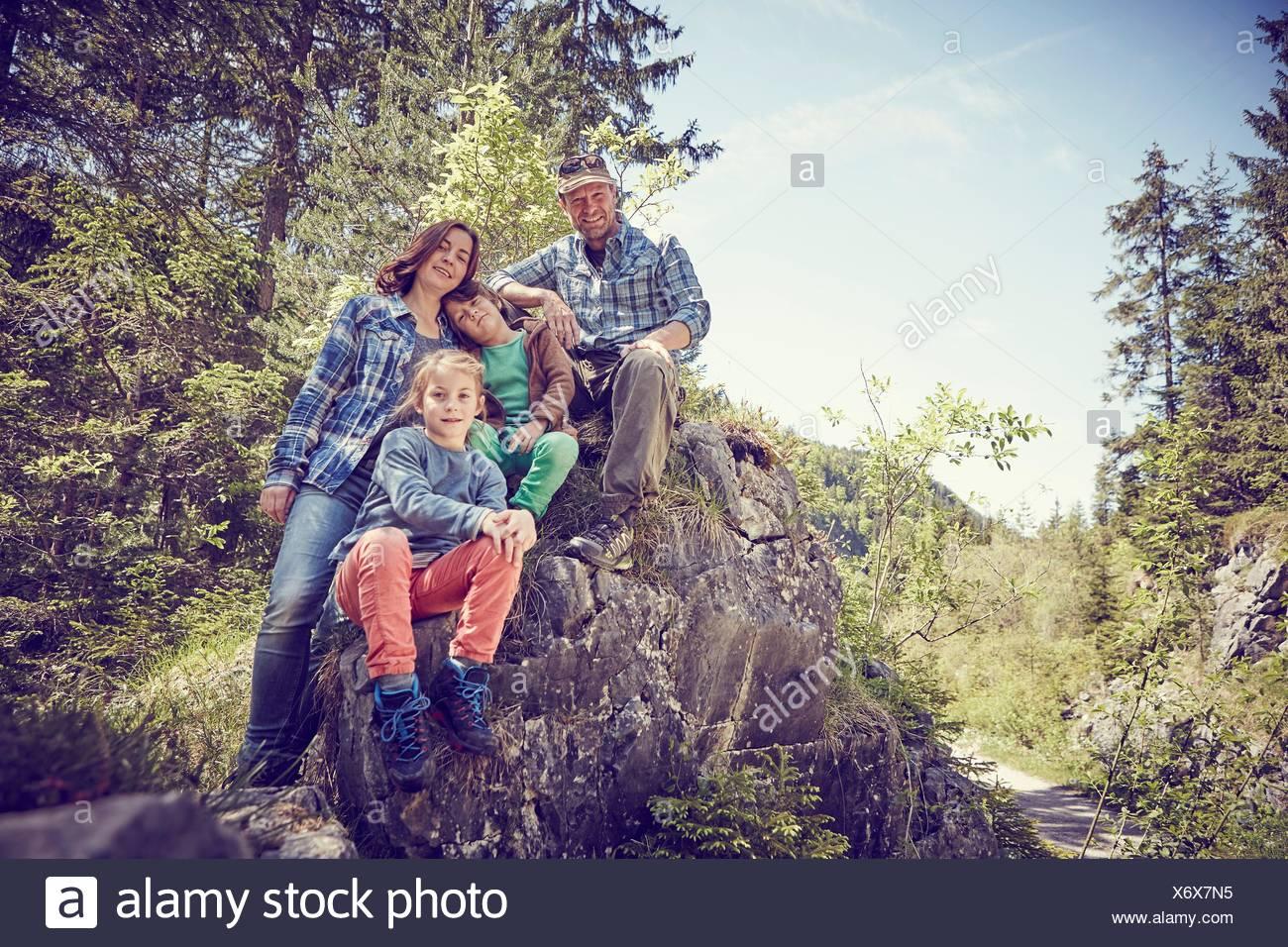 Ritratto di famiglia seduta su roccia nella foresta Immagini Stock