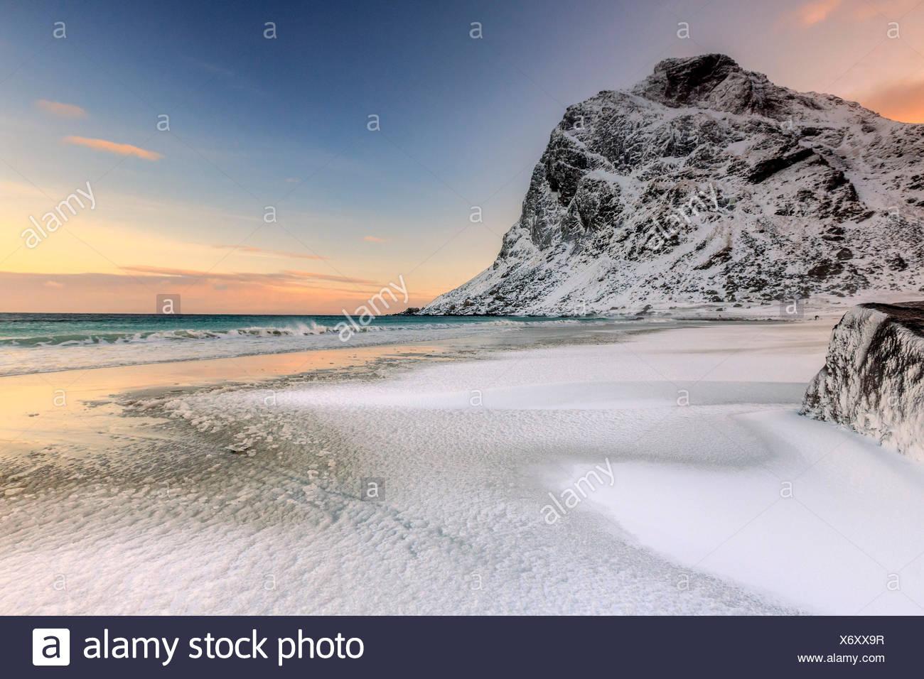 Onde avanza verso la riva del mare circondato da vette innevate all'alba. Uttakleiv Isole Lofoten in Norvegia Europa Immagini Stock