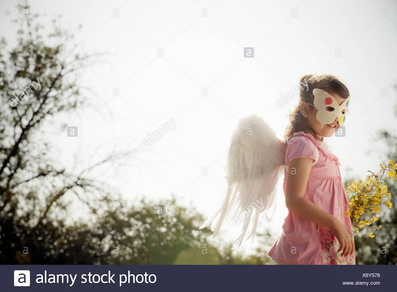 La ragazza di angelo ali e la maschera per il viso Immagini Stock
