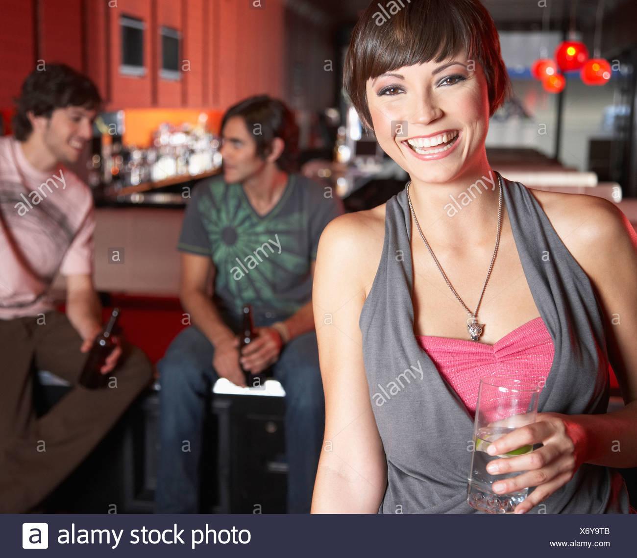 Donna con la bevanda in piedi da tavoli da biliardo sorridente Immagini Stock