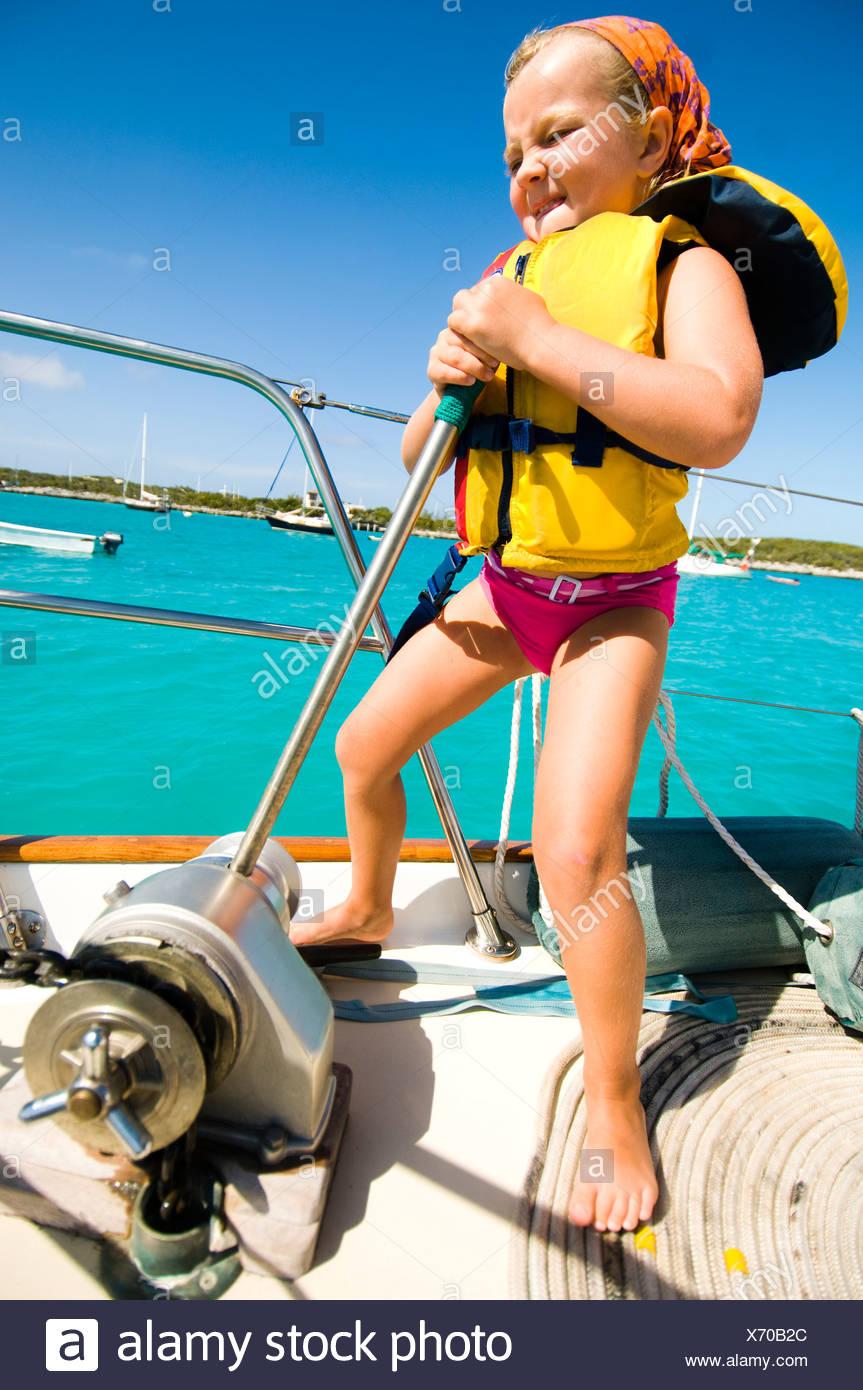 Una giovane ragazza aiuta a portare l'ancora prima che un giorno la vela con la sua famiglia Immagini Stock