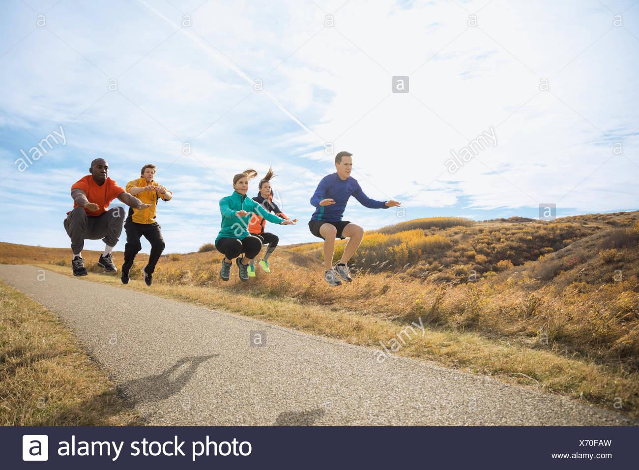 Gruppo di fitness di saltare sul percorso rurale Immagini Stock