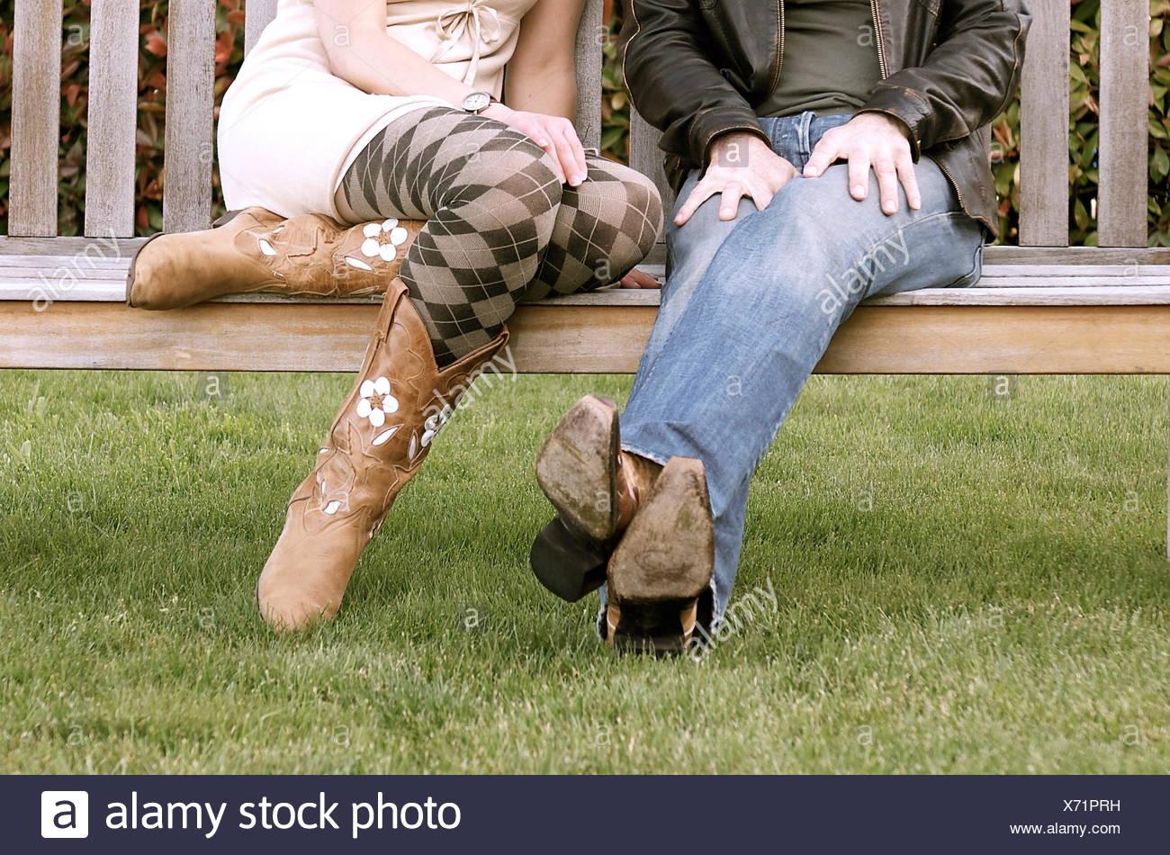 Sezione bassa di un paio di indossare stivali da cowboy di seduta su una panchina Immagini Stock