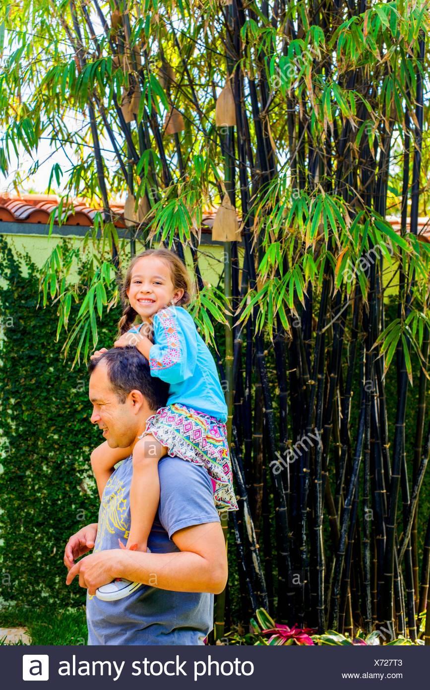 Ritratto di ragazza ottenendo una spalla trasportare dal padre nel giardino Immagini Stock