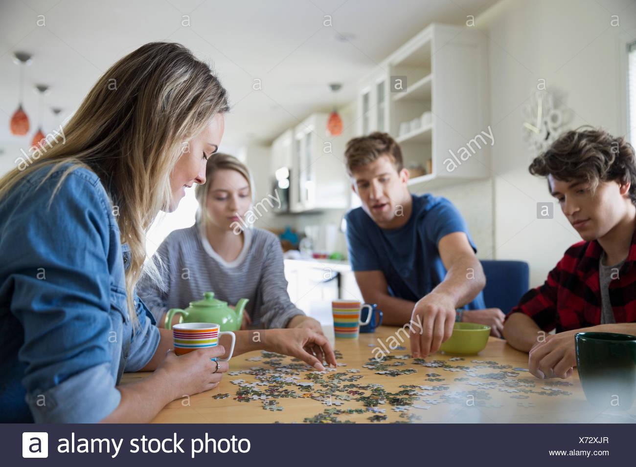 Coppie giovani assemblaggio di Jigsaw Puzzle al tavolo da pranzo Immagini Stock