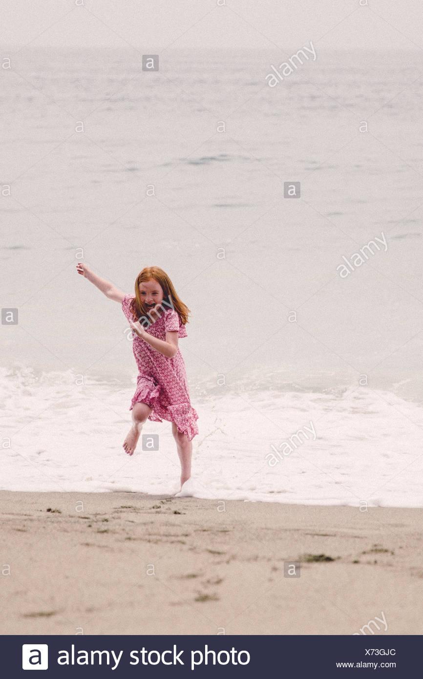 La ragazza (6-7) di scappare dalle onde Foto Stock
