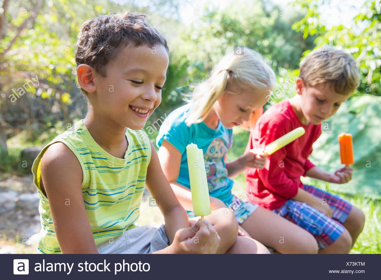 Tre bambini in giardino a mangiare ghiaccioli Immagini Stock