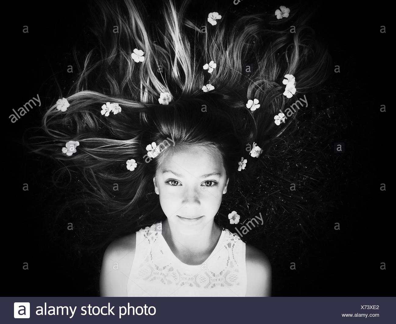 Ritratto di ragazza distesa verso il basso con i fiori nei capelli Foto Stock