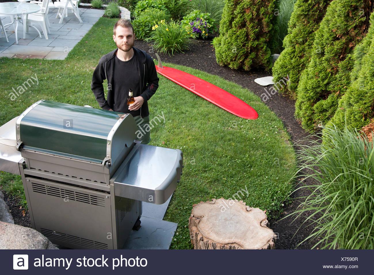 Ritratto di metà uomo adulto in piedi da barbecue con bottiglia di birra in giardino Immagini Stock