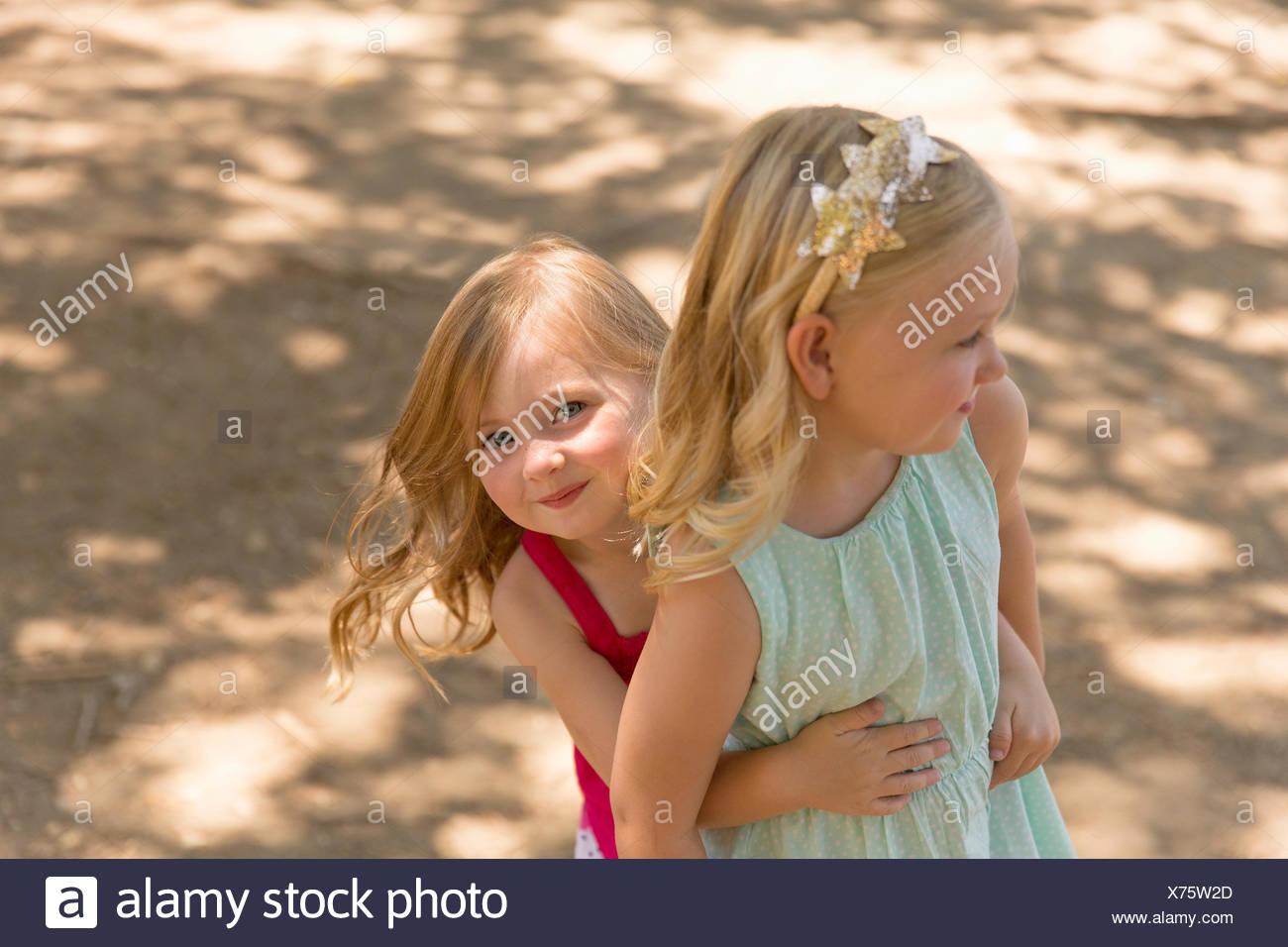 Ragazza giovane di nascondersi dietro la sorella in posizione di parcheggio Immagini Stock