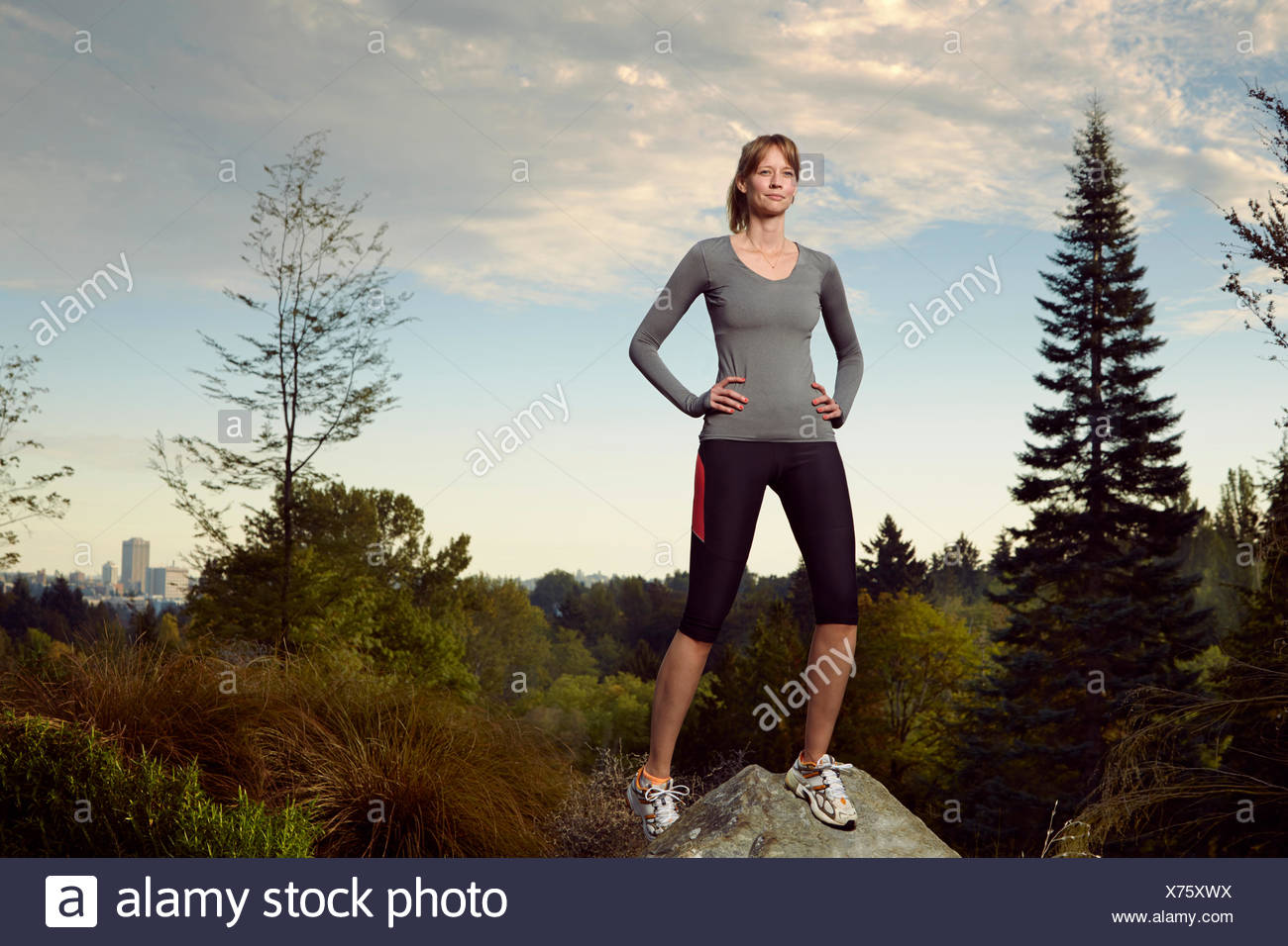 Ritratto di donna runner sulla parte superiore di boulder in posizione di parcheggio Immagini Stock