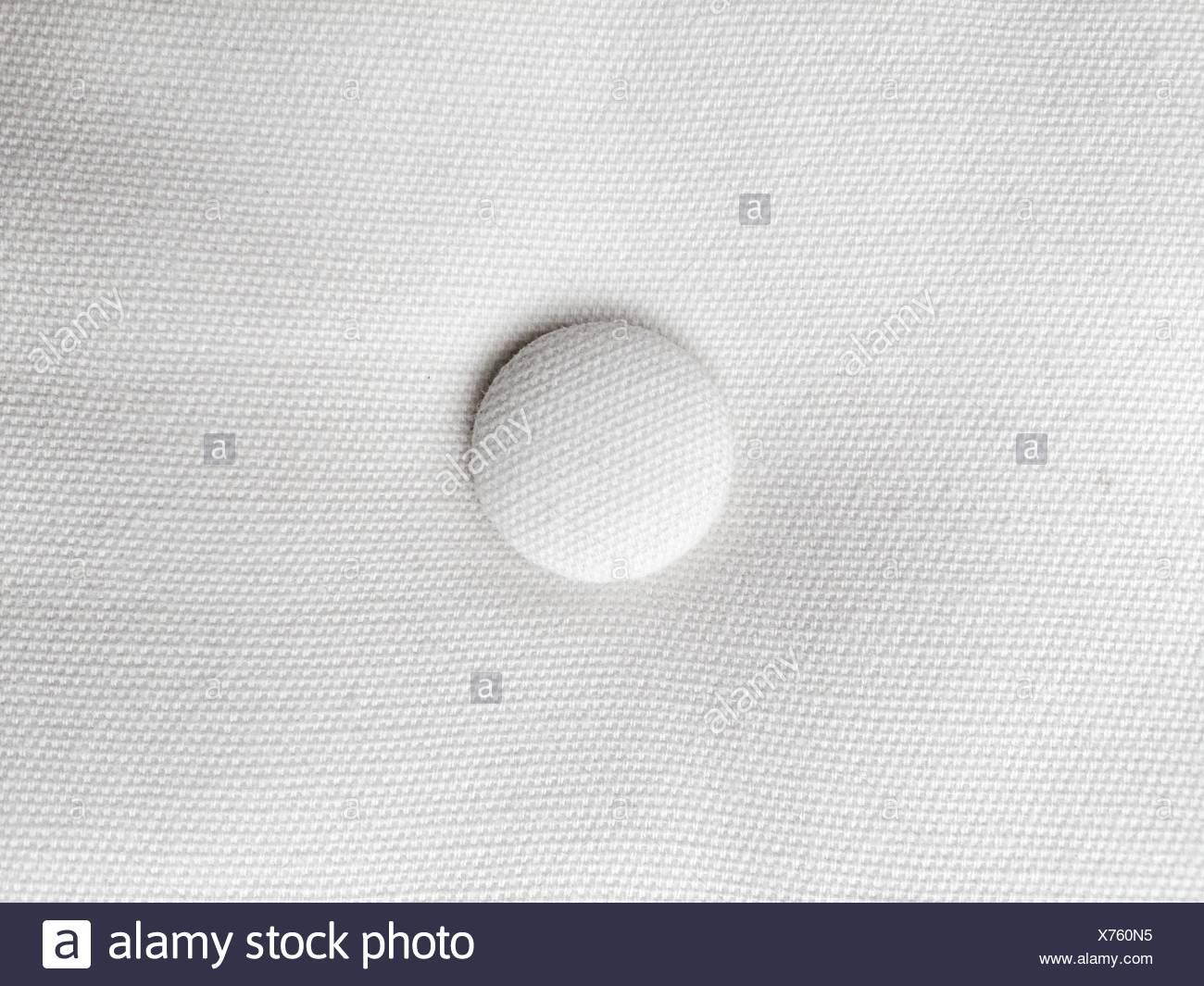 Close-Up del pulsante sul tessuto bianco Immagini Stock